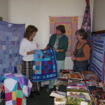 Chalford Stitchers hand over Stroud Refuge quilts.