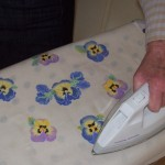 Ironing bondawebbed pieces onto a backing as part of the process of applique