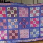 A quilt made from hand-pieced 9-square blocks, sashed and completed by machine.
