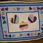 A quilt making use of some applique hearts that were surplus to requirements.