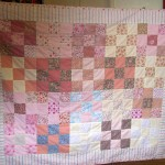 A group quilt, mostly hand-stitched.